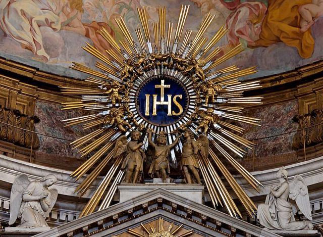 IHS monogram, with kneeling angels, atop the main altar, Church of the Gesù, Rome_en.wikipedia.org